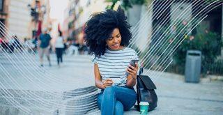Une cliente visiblement satisfaite de son transfert d'argent effectué via le service XE